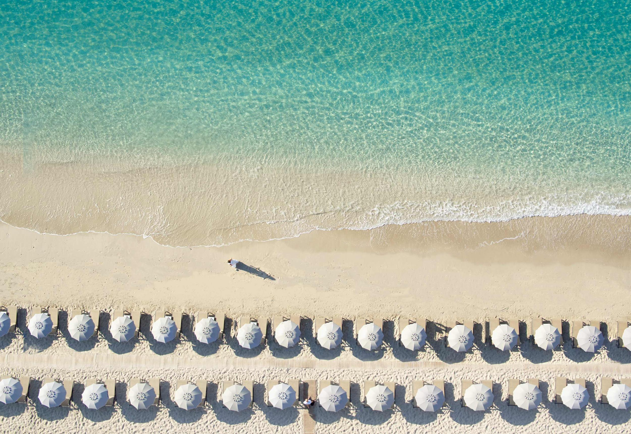 aerial view of Parga Beach, woman walking on the beach, umbrellas, tourquois water