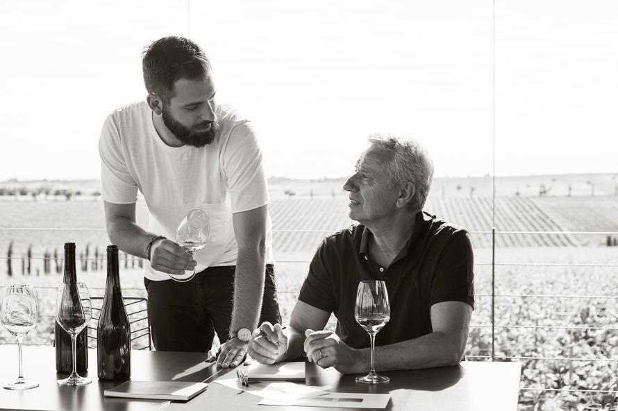 Vaggelis Gerovassiliou and son tasting wine in front of vinyard
